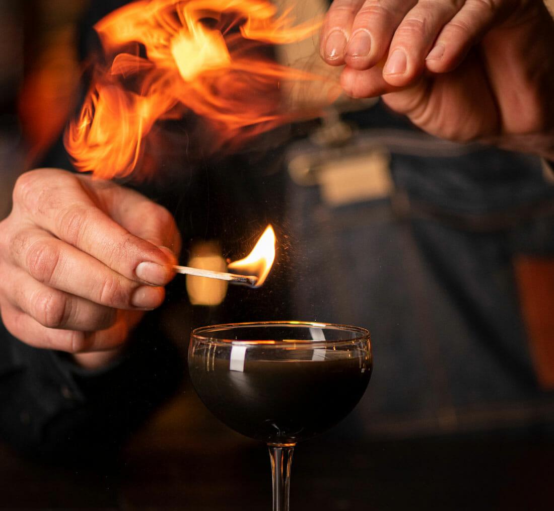 igniting an orange rind over a Corralejo dark reviver cocktail